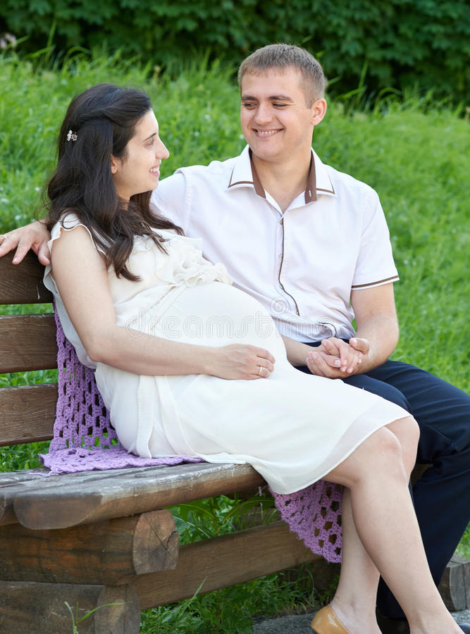 Happy couple in summer city park outdoor, pregnant woman, bright sunny day and green grass, beautiful people portrait royalty free stock photography