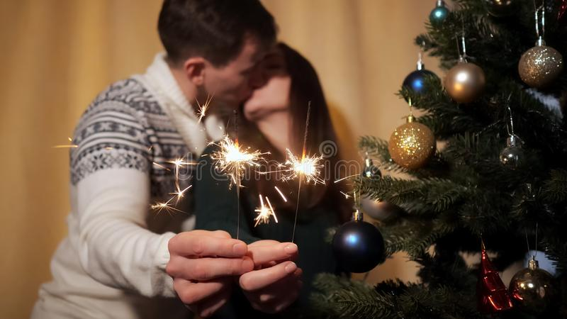 Happy couple in sweaters hold bright sparklers near camera royalty free stock photography