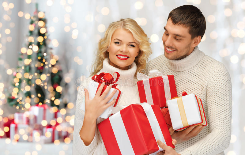 Happy couple in sweaters holding christmas gifts royalty free stock photos