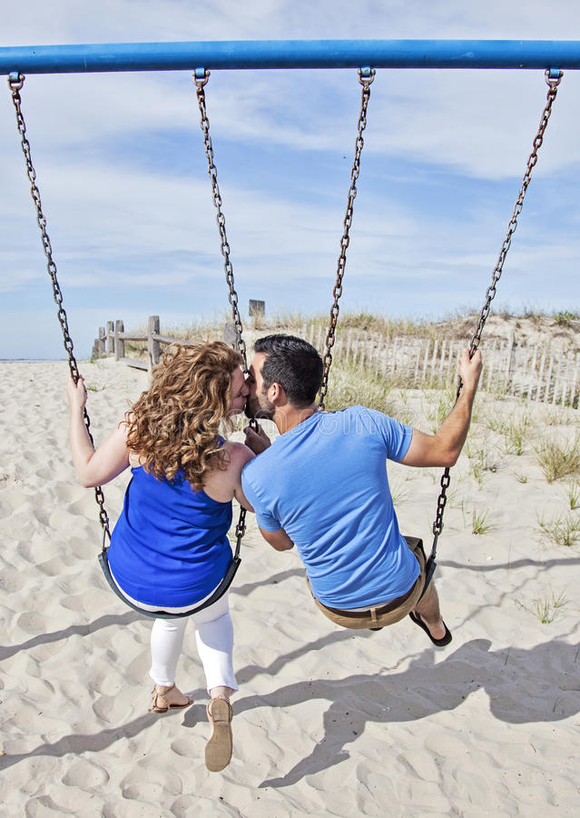 Happy couple on swings. Back view of couple kissing on a swing set on the beach royalty free stock images
