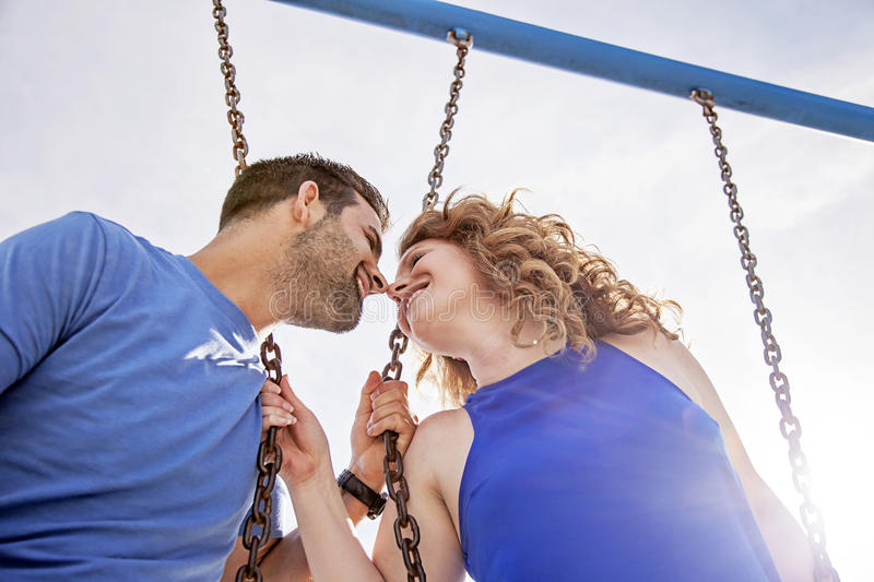 Happy couple on swings in summer. Smiling couple face to face on swing set on sunny day