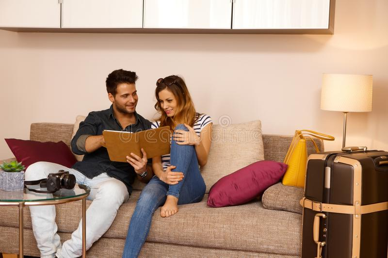 Happy couple with tablet on holiday stock photos