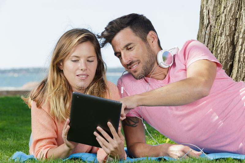 Happy couple with tablet lays on ground stock photos