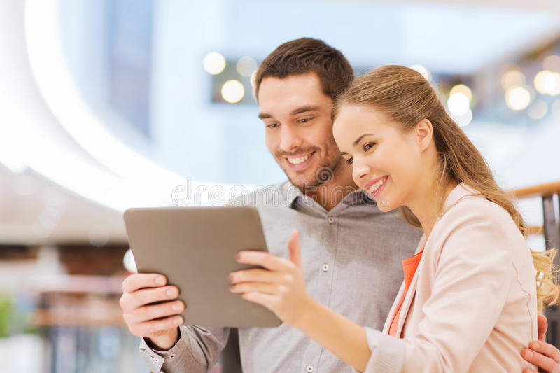 Happy couple with tablet pc taking selfie in mall royalty free stock photography
