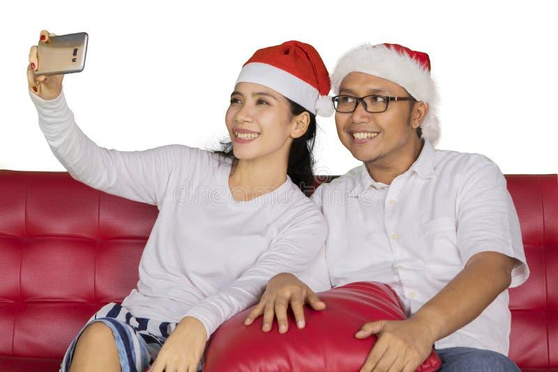 Happy couple taking photo at Christmas day stock photo