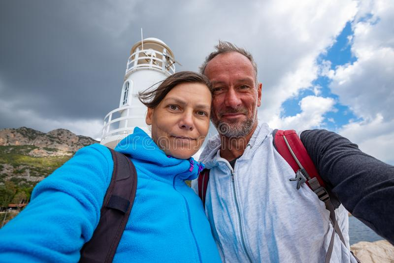 Happy couple taking selfie on the background of the lighthouse stock image