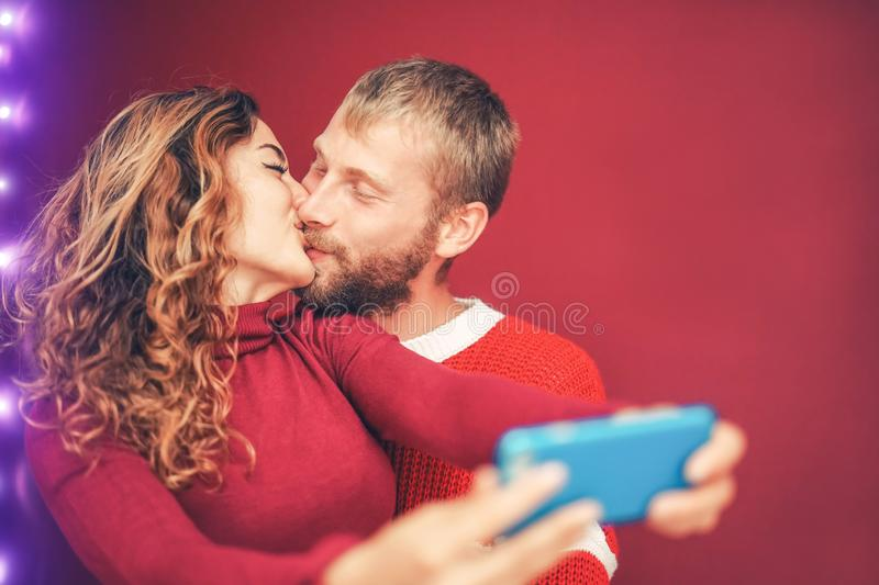 Happy couple taking selfie with mobile smartphone camera - Young romantic lovers kissing and celebrating Christmas holidays. Love relationship, xmas and royalty free stock photo