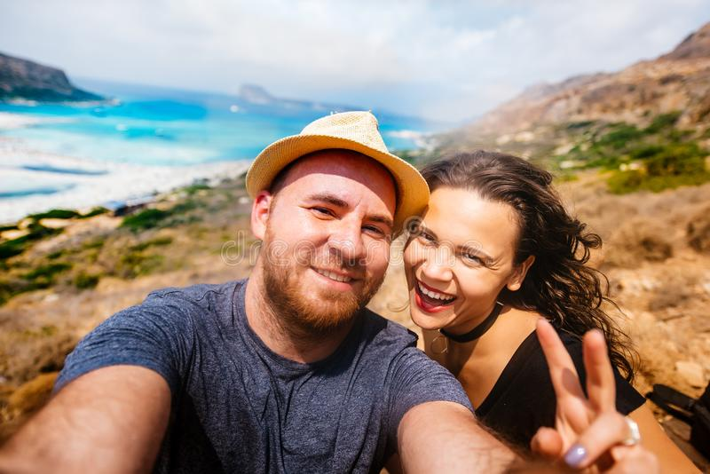 Happy couple taking selfie photo with island and turquoise water. Self portrait of couples in vacation. Young happy couple taking selfie photo with island and royalty free stock photography