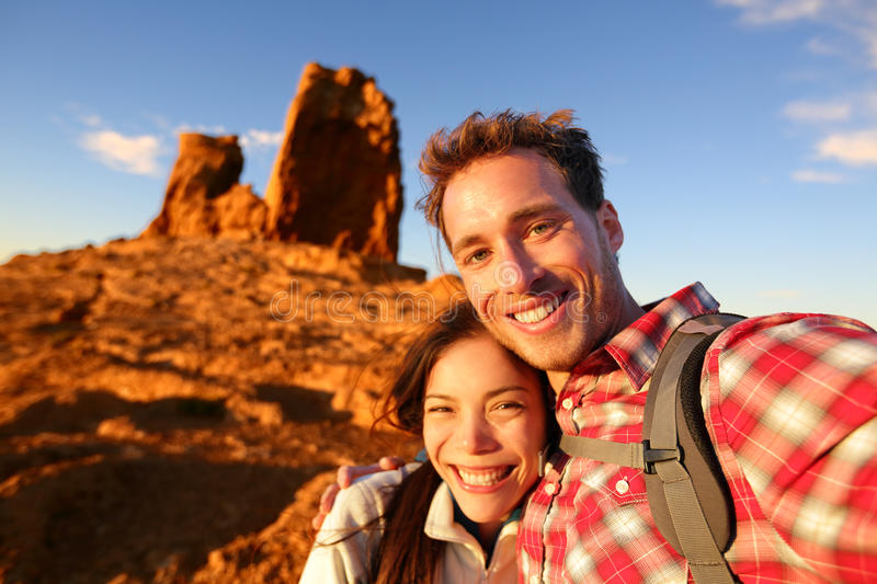 Happy couple taking selfie self portrait hiking. Happy couple taking selfie self-portrait photo hiking. Two friends or lovers on hike smiling at camera outdoors stock photography