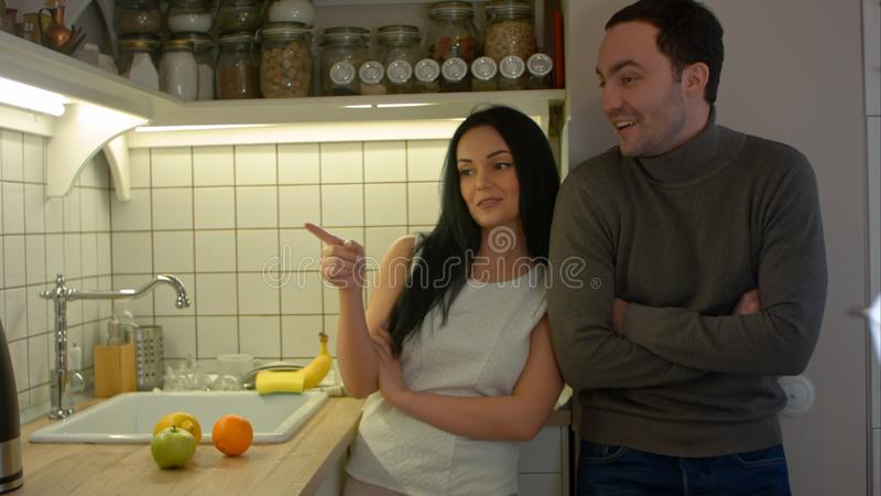 Happy couple talking while cooking in kitchen at home royalty free stock photo