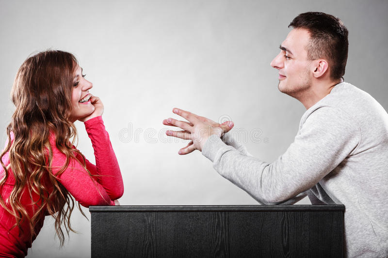 Happy couple talking on date. Conversation. Happy couple talking and laughing on date. Smiling girl and guy having conversation. Amusing men making women laugh stock photography