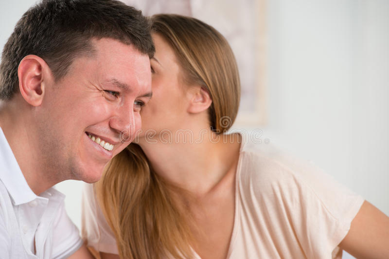 Happy couple talking and gossiping in their living room stock photography