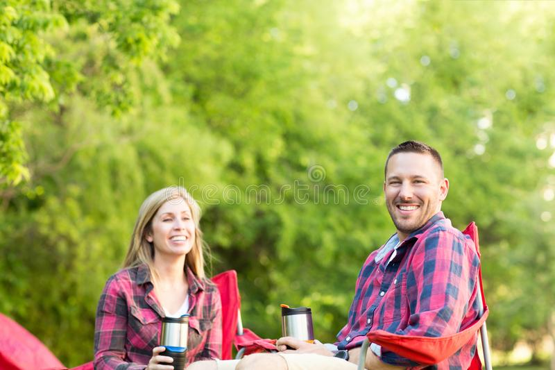 Couple talking and laughing on a camping trip. Happy couple talking and laughing on a camping trip royalty free stock photography