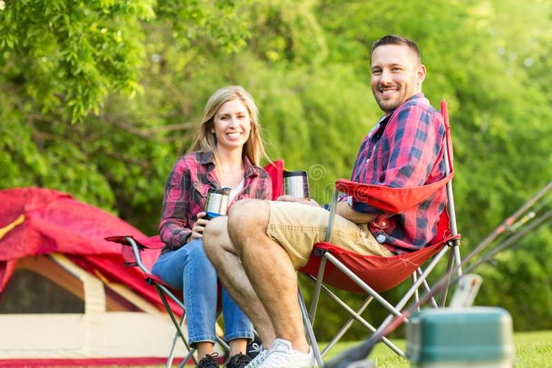 Couple talking and laughing on a camping trip. Happy couple talking and laughing on a camping trip stock image