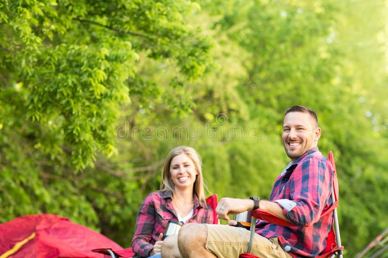 Couple talking and laughing on a camping trip. Happy couple talking and laughing on a camping trip stock images