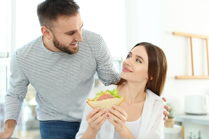 Happy couple with tasty sandwich stock image