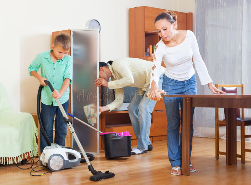 Happy couple and teenager cleaning. Happy couple and teenager boy cleaning with vacuum cleaner in living room stock image