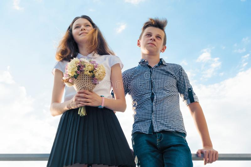 Happy couple of teens boy and girl 14, 15 years old. Young people smiling and talking, blue sky background.  stock images