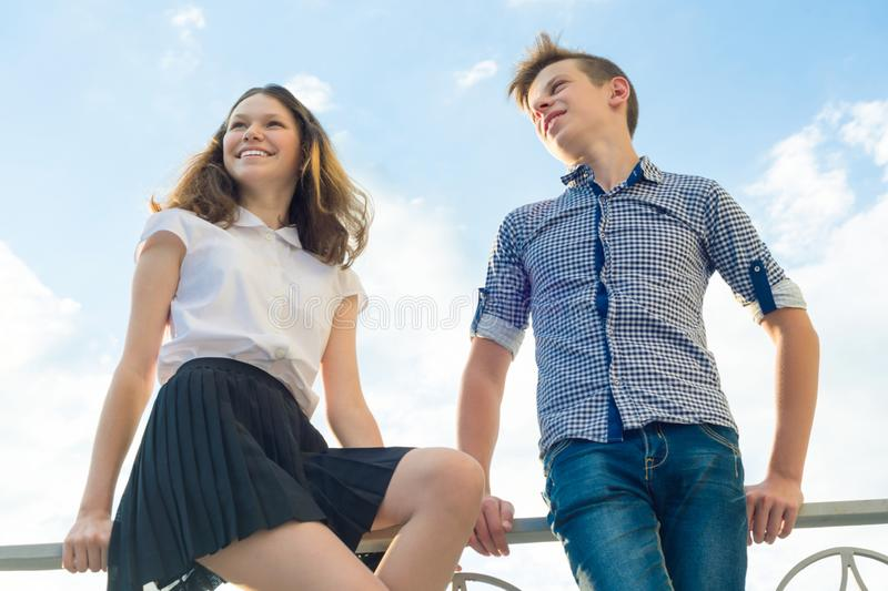 Happy couple of teens boy and girl 14, 15 years old. Young people smiling and talking, blue sky background.  royalty free stock photo