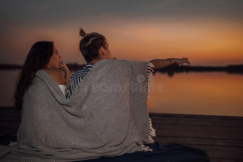 Happy couple of teens enjoying in romantic date while sitting covered with blanket during sunset royalty free stock images