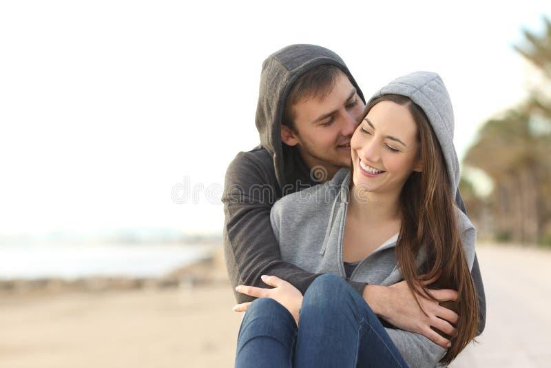 Happy couple of teens flirting on the beach stock photos