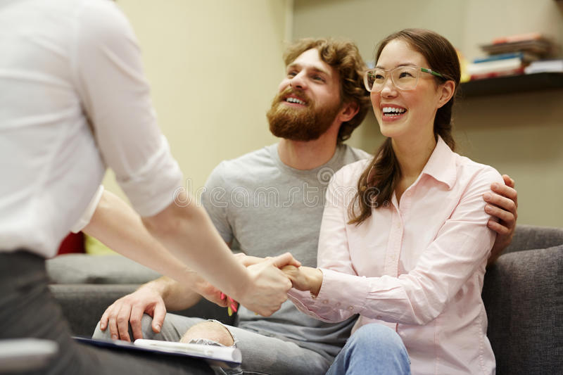 Happy Couple Thanking Advisor for Session. Portrait of young men and women smiling happily thanking psychiatrist at couples counseling session stock photography