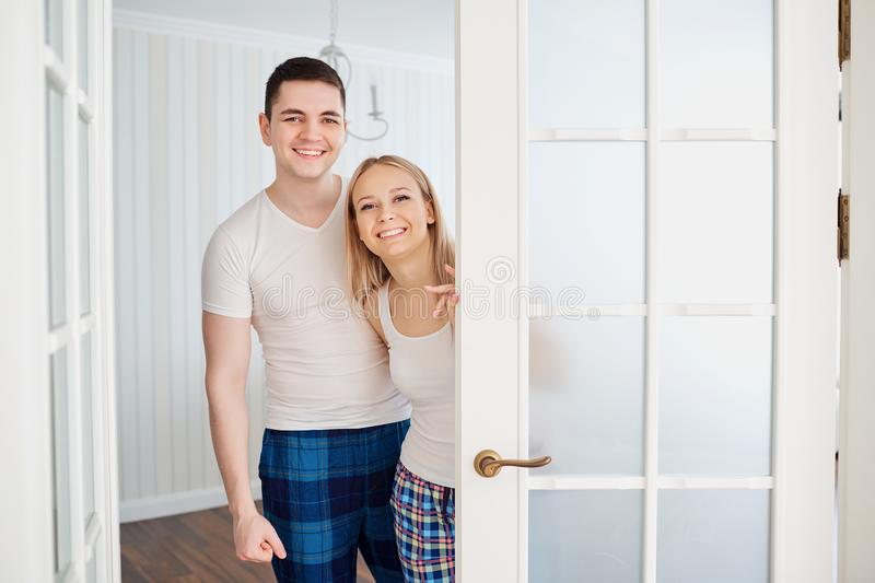 A happy couple in their pajamas invites to their house. stock photography