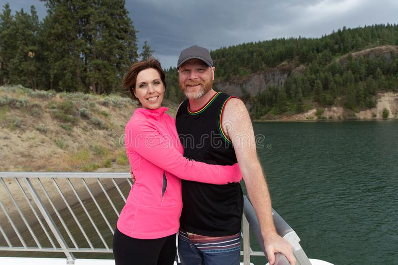 Happy couple together on a lake royalty free stock images