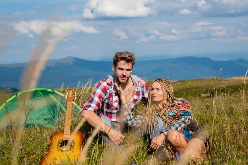 Happy couple tourists man and woman having a rest beside camp, guitar and sunny day. Travel couple enjoying wanderlust stock image