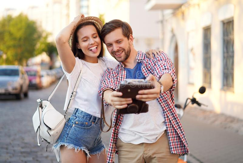 Happy couple of tourists photographing a selfie in a city street in a sunny day. royalty free stock photos