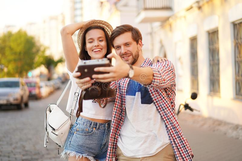 Happy couple of tourists photographing a selfie in a city street in a sunny day. stock photography