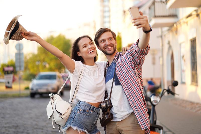 Happy couple of tourists photographing a selfie in a city street in a sunny day. stock photo