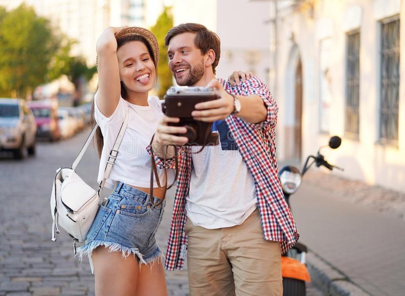 Happy couple of tourists photographing a selfie in a city street in a sunny day. royalty free stock photography