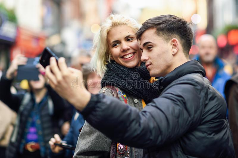 Happy couple of tourists taking selfie in a crowded street. Happy couple of tourists taking selfie in a crowded street of London royalty free stock photography
