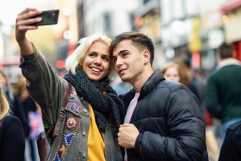Happy couple of tourists taking selfie in a crowded street. Happy couple of tourists taking selfie in a crowded street of London stock image