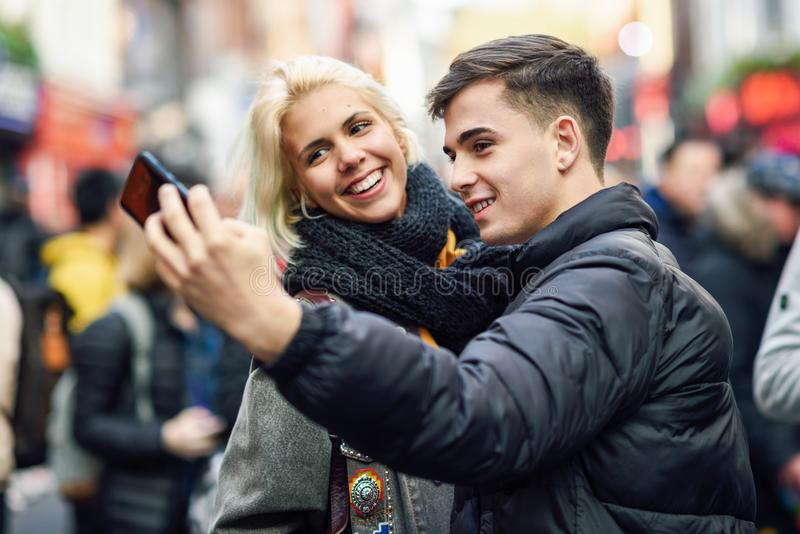 Happy couple of tourists taking selfie in a crowded street. Happy couple of tourists taking selfie in a crowded street of London stock photography