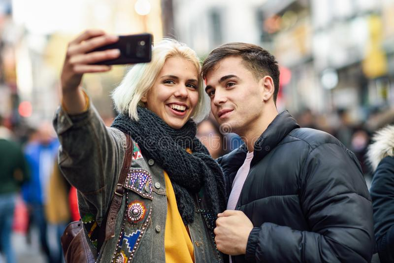 Happy couple of tourists taking selfie in a crowded street. Happy couple of tourists taking selfie in a crowded street of London royalty free stock image