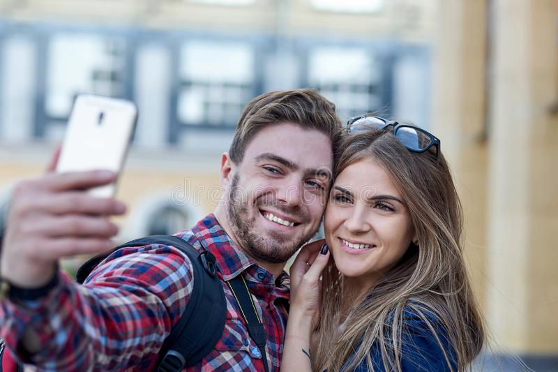 Happy couple of tourists taking selfie in showplace of city. Man and woman making photo on city background royalty free stock photo