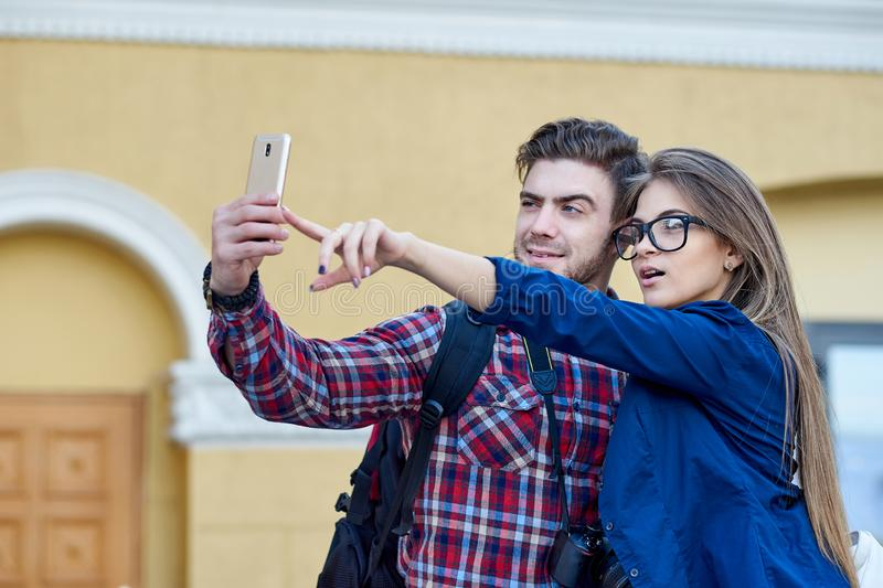 Happy couple of tourists taking selfie in showplace of city. Man and woman making photo on city background stock photo