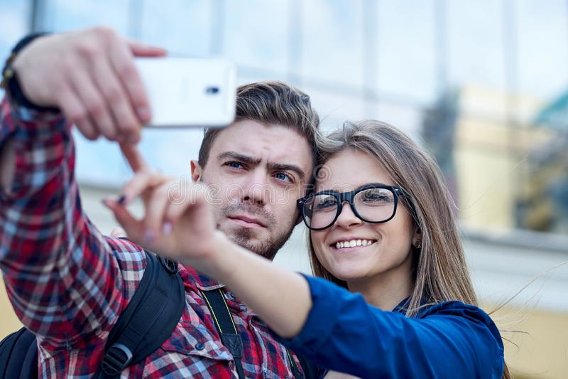 Happy couple of tourists taking selfie in showplace of city. Man and woman making photo on city background stock photos