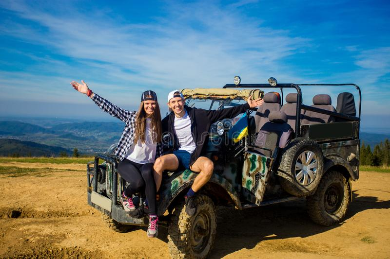 Happy couple travel by car on mountains top. stock images