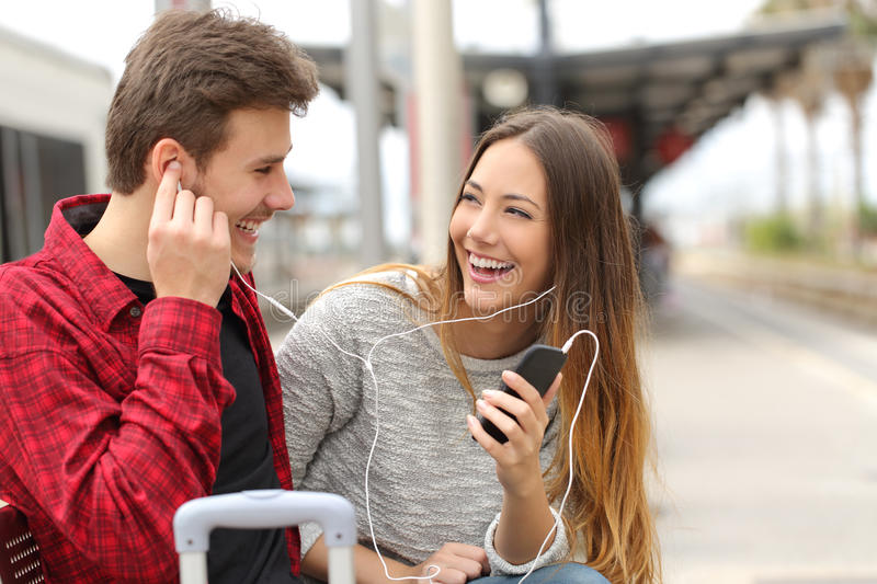 Happy couple of travelers sharing music on holidays stock images