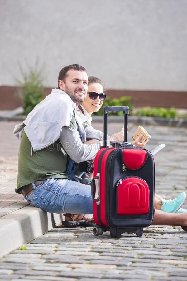 Happy Couple Traveling Around City. Having Lunch with Sandwiches royalty free stock photo