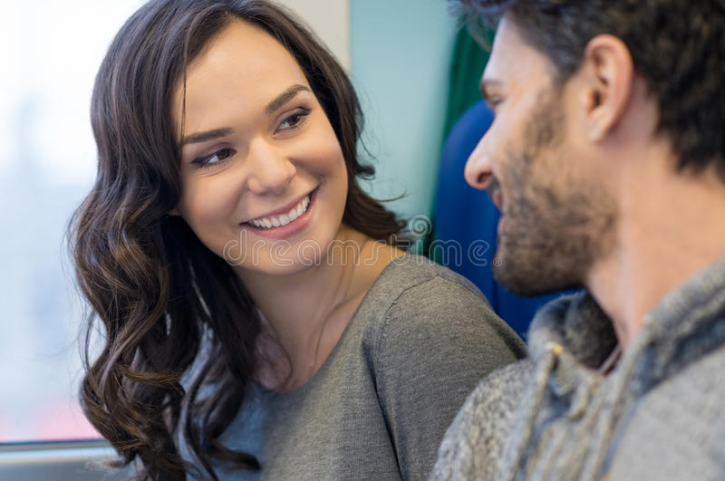 Happy couple traveling. Smiling young couple looking at each other and smiling in train while travelling together. They are sit near the window and she is stock images