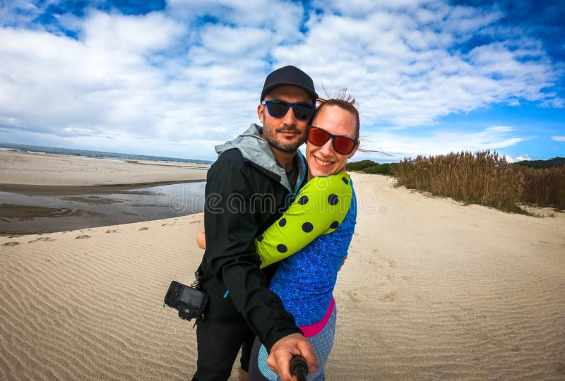 Happy couple travelling making self portrait selfie on sandy beach. Young happy explorers with sunglasses taking photo on sunny day with Atlantic sea stock photo