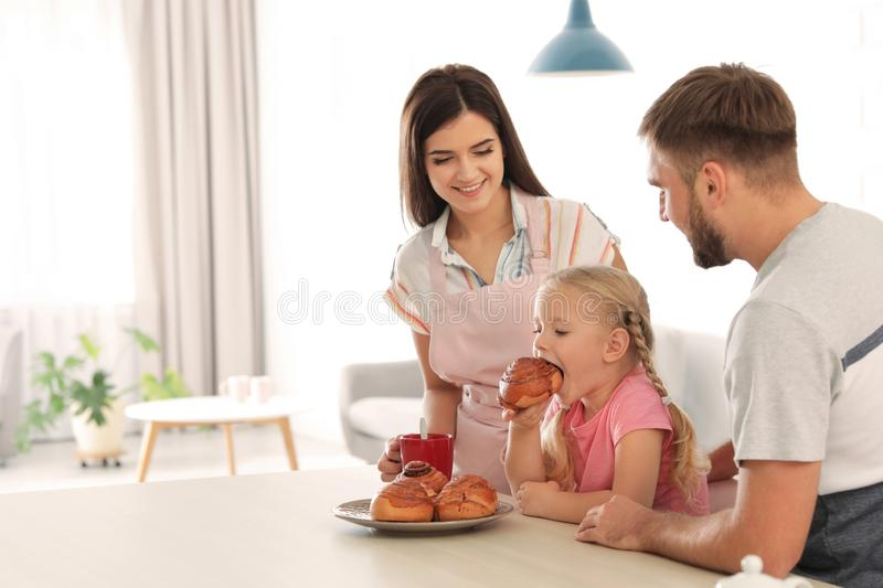 Happy couple treating their daughter with freshly oven baked bun. In kitchen stock photo