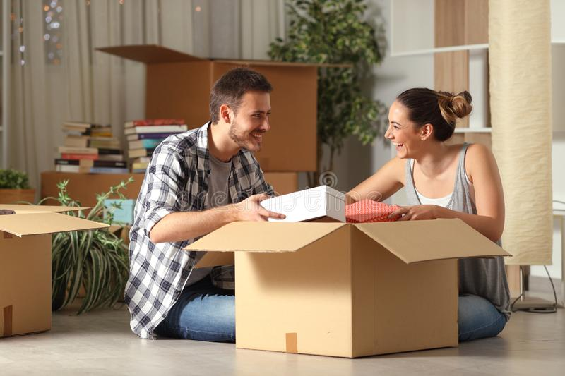Happy couple unboxing belongings moving house looking each other royalty free stock image