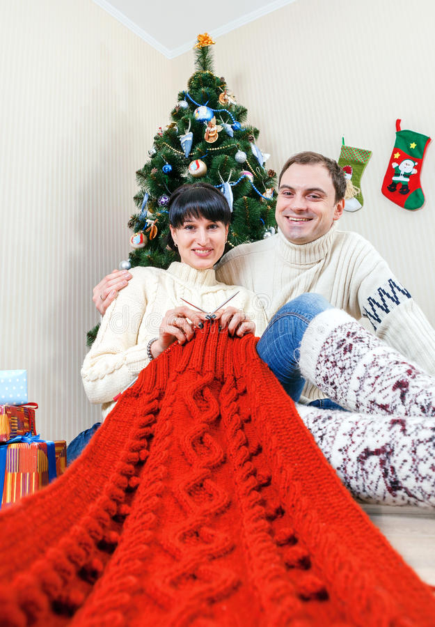 Happy couple under christmas tree with knitting work stock photos