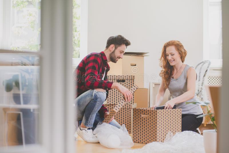 Happy couple unpacking stuff after relocation to new home stock image