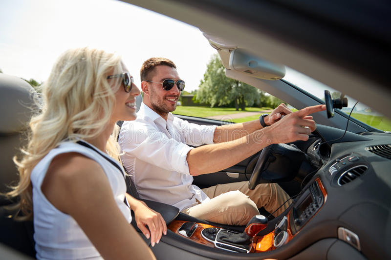 Happy couple using gps navigation system in car. Road trip, leisure, travel, technology and people concept - happy men and women driving car and using gps stock images